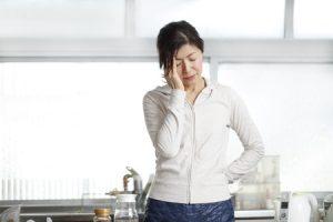 肩こりから来る頭痛でこめかみが痛い女性の写真
