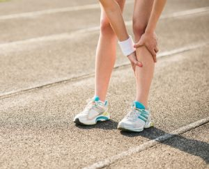 陸上競技場でシンスプリントですねが痛くてすねを押さえている女性ランナーの写真