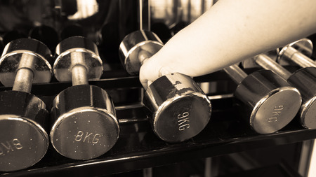 43007554 - chubby man holding rustic dumbell 5 kg in gym copper black and white