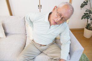 腰痛で腰を痛がる男性の写真