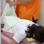 横浜西区保土ヶ谷神奈川区近くの宮谷小交差点前整骨院の自費治療でストレッチ治療をしている女性の写真