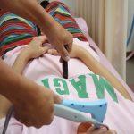 遠絡(えんらく)療法で首にレーザー治療をしている写真