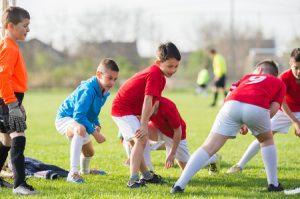 オスグット・成長痛の膝のストレッチをしている成長期のサッカー少年の写真