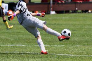 オスグットになり易い成長期のサッカーのゴールキーパーがサッカーボールを蹴る写真