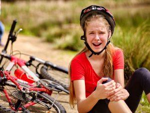 自転車で転倒して膝を打撲して痛がる少女の写真