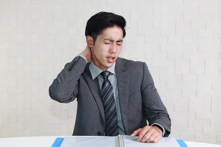寝違えて首が硬くなり易いデスクワークの男性の写真
