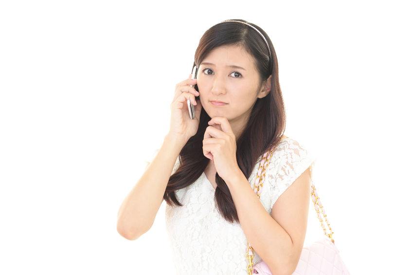 遠絡(えんらく)療法の治療を電話予約する女性の写真