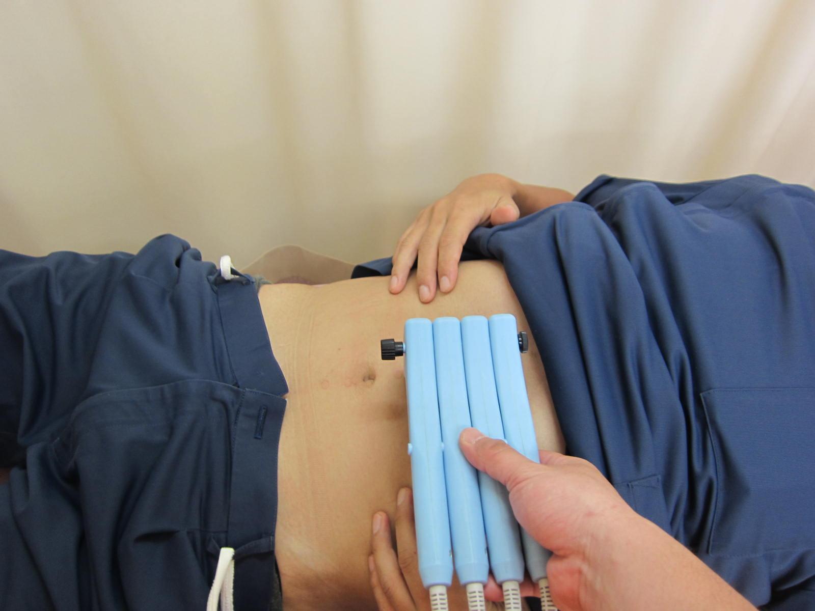 膝が痛い男性が遠絡(えんらく)療法の治療をしている写真