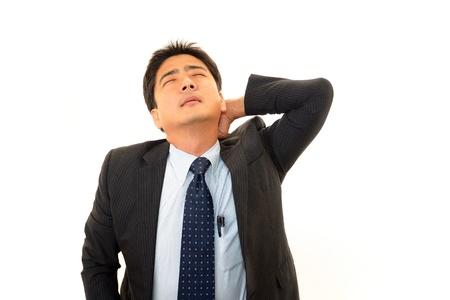 寝違えをして首が痛いサラリーマンの写真