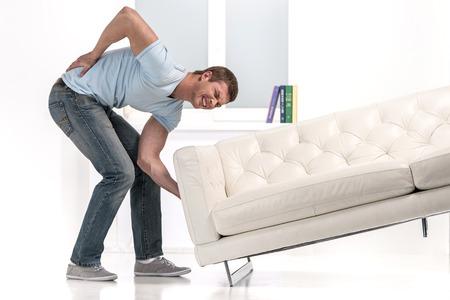 ソファーを持ち上げようとして腰が痛いぎっくり腰になった男性の写真