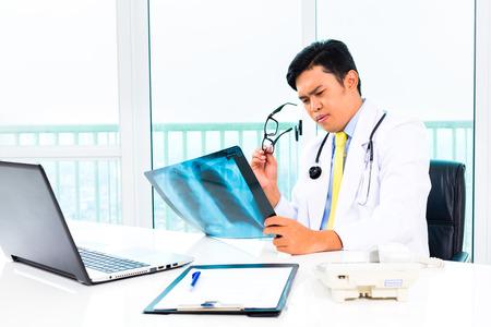 腰椎分離症の腰のレントゲン写真を見ている医師