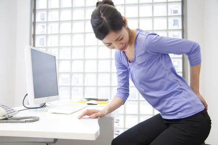 ぎっくり腰になりやすい椅子から不意に立ち上がった動作の女性の写真