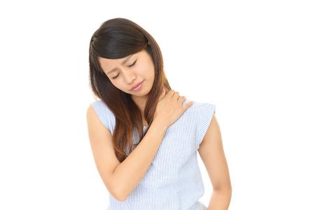 肩こりで肩が痛い人が寝違えをした女性の写真