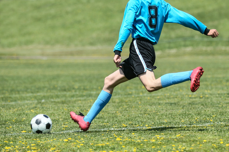 腰椎分離症の原因の腰を反り捻じるサッカーのボールを蹴る写真