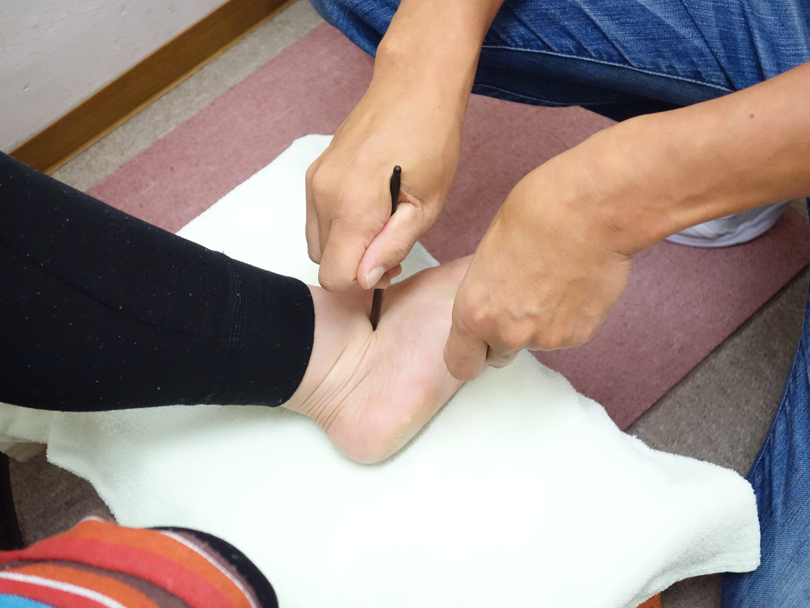 遠絡(えんらく)療法で寝違えの治療をしている女性の写真