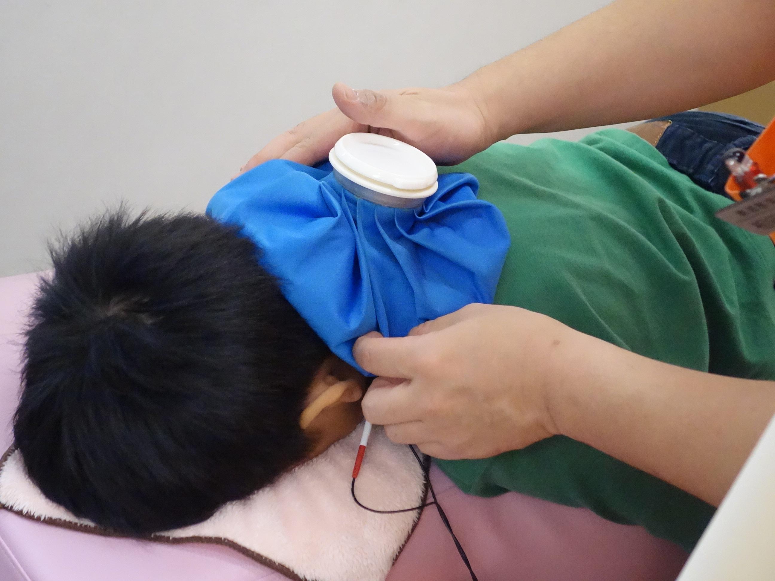 寝違えの炎症を引かせる電気治療とアイシングをしている写真
