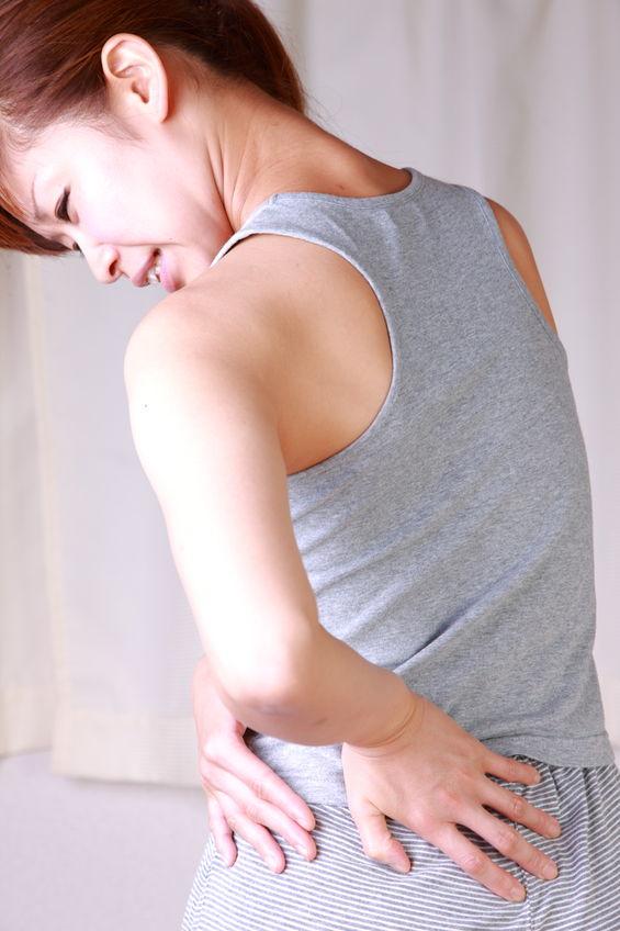 腰椎分離症に多い腰を捻り腰が痛い女性の写真