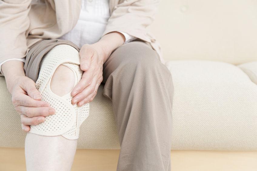 膝が痛い人が膝のサポーターをする写真