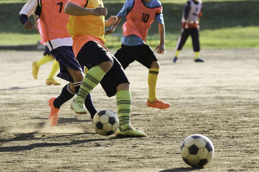 オスグットになり易い成長期のサッカーのサッカーボールを蹴る写真
