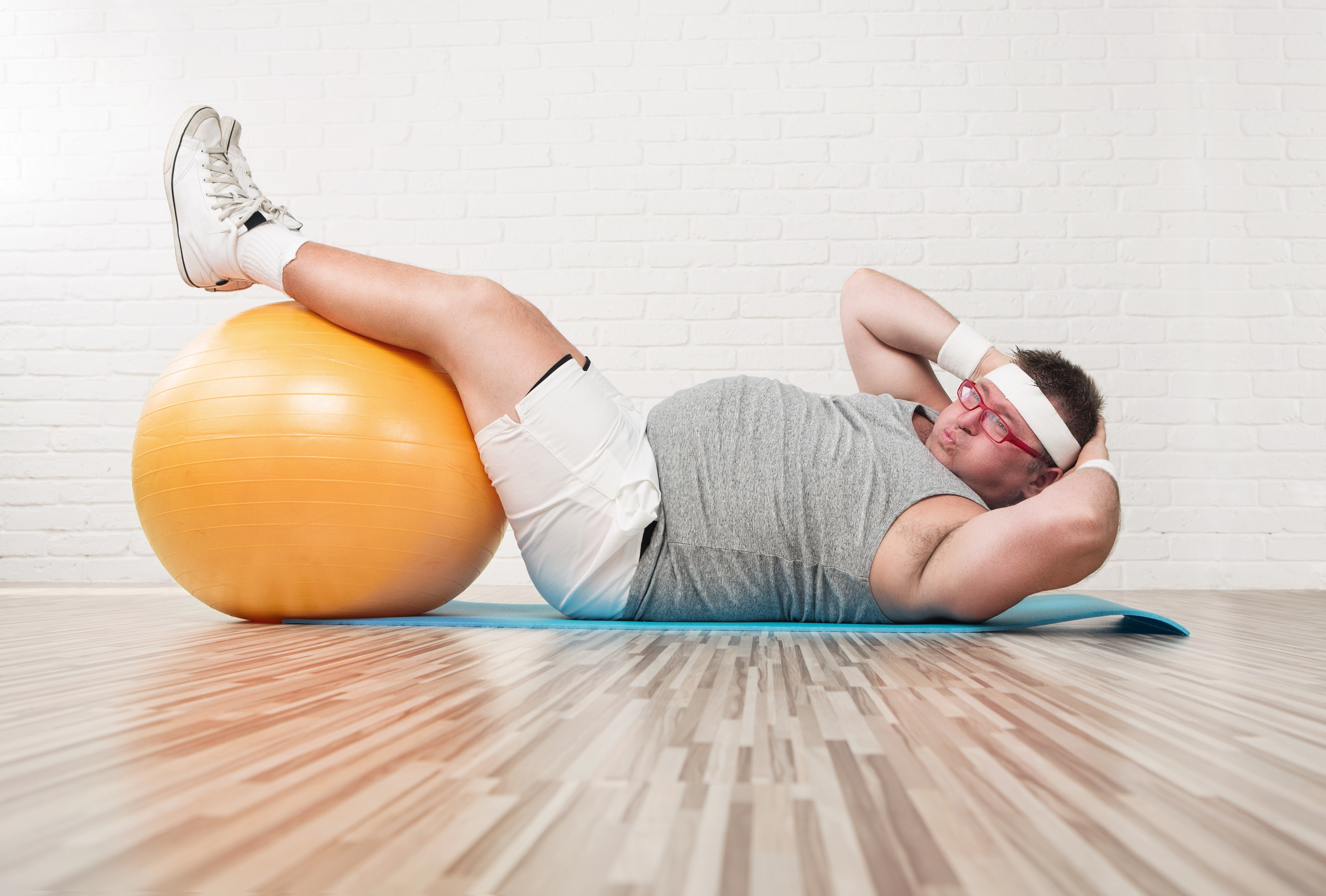 運動不足で頭痛の人が腹筋運動をしている写真