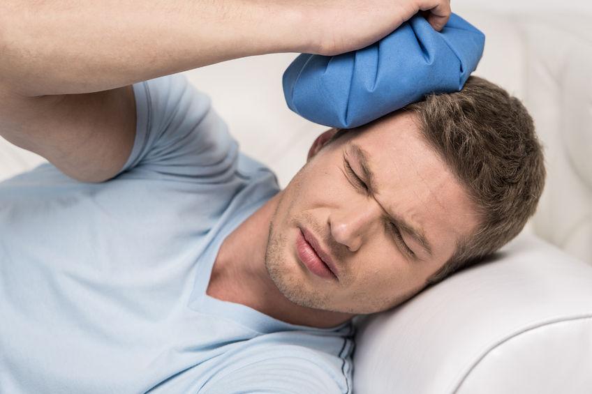 頭痛の男性が頭を氷嚢で冷やしている写真